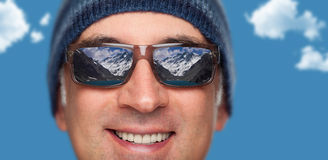 Close up of a man's face wearing sunglasses. With a reflection of snow mountains on them Stock Photo