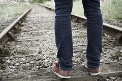 Close-Up Of Man's Feet Standing Between Railway Tracks Stock Images