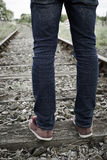 Close-Up Of Man's Feet Standing Between Railway Tracks Royalty Free Stock Image