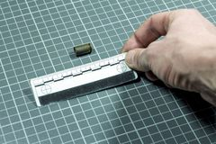The man`s hand applies the forensic ruler to the cartridge case without a bullet from the pistol for the ballistic examination. C. Close-up.The man`s hand stock image
