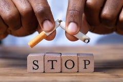 Man Breaking Cigarette Over Wooden Stop Blocks. Close-up Of A Man's Hand Breaking Cigarette Over Wooden Stop Blocks stock image