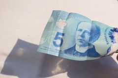 A close up of man`s hand and Canadian money- $5.00 bill. Canadian $5.00 currency. Close up of Sir Wilfrid Laurier. This picture can be used as a magazine front royalty free stock photos