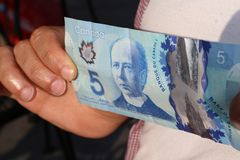 A close up of man`s hand and Canadian money- $5.00 bill. Canadian $5.00 currency. This picture can be used as a magazine front cover or billboard for anything to royalty free stock photos