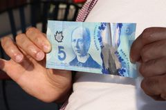 A close up of man`s hand and Canadian money- $5.00 bill stock photography