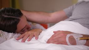Sick man stroking sleeping wife in clinic