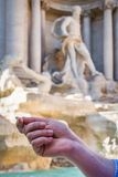 Close up of a man`s hand holding a coin in front of Fountain Di Trevi in Rome, Italy. Close up of a man`s hand holding a coin in front of Fountain Di Trevi in Stock Images