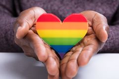 Rainbow Heart On The Man`s Hand. Close-up Of Man`s Hand Holding Colorful Striped Painted Heart stock photo
