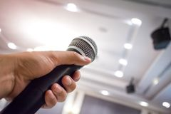Close up of man`s hand holding microphone in conference hall or stock image