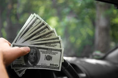 Close-up of a man`s hand with money. A rich businessman driving a new car on a blurred park background. Wealth concept. Close-up of man`s hand holding new stock photos