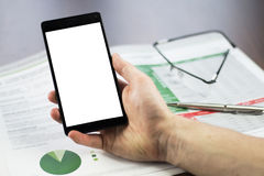 Close up of a man`s hand holding smartphone with documents, glas. Ses and pen on the office table Royalty Free Stock Photography