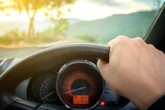 Close-up of man's hand holding steering wheel of a car and empty Stock Photo