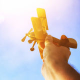 Close up of man& x27;s hand holding toy airplane against blue sky. Close up photo of man& x27;s hand holding toy airplane against blue sky Royalty Free Stock Photos