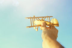 Close up of man& x27;s hand holding toy airplane against blue sky. Close up photo of man& x27;s hand holding toy airplane against blue sky Stock Photography
