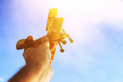 Close up of man& x27;s hand holding toy airplane against blue sky. Close up photo of man& x27;s hand holding toy airplane against blue sky Royalty Free Stock Image