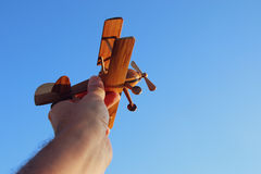 Close up of man& x27;s hand holding wooden toy airplane against blue sky. Close up photo of man& x27;s hand holding wooden toy airplane against blue sky Stock Images