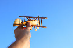 Close up of man& x27;s hand holding wooden toy airplane against blue sky. Close up photo of man& x27;s hand holding wooden toy airplane against blue sky Royalty Free Stock Image