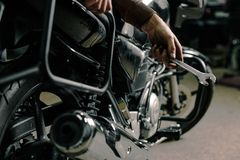 Hand with wrench near motorcycle. Close up of man`s hand holding wrench. Fixing motorcycle concept Royalty Free Stock Photos