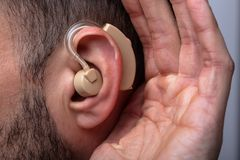 Man Inserting Hearing Aid In His Ear. Close-up Of A Man`s Hand Inserting Hearing Aid In His Ear royalty free stock image