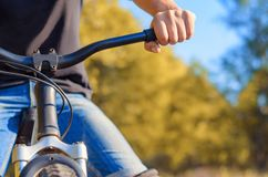 Close-up of a man`s hand in jeans and a black T-shirt on the ste. Ering wheel of an off-road bicycle. Walk in the open air in the fall Royalty Free Stock Photography