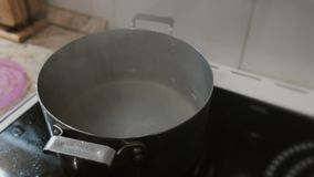Close-up of a man`s hand opens the lid of a pot of boiling water. Close-up of a man`s hand opens the lid of a pot of boiling water stock video footage