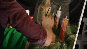 Close up of man`s hand painting still life picture on canvas in art studio.  stock video footage