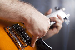 Close up on man`s hand playing guitar Stock Photos