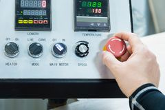 Close-up of a man`s hand on a red button on the control panel. Emergency stop or start of equipment and production.  stock photo