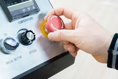 Close-up of a man`s hand on a red button on the control panel. Emergency stop or start of equipment and production.  stock photos