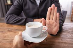 Man Refusing Cup Of Coffee Offered By Person. Close-up Of A Man`s Hand Refusing Cup Of Coffee Offered By Person Over Wooden Desk stock image