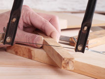 Close-up of man's hand sawing wooden plank Stock Photography