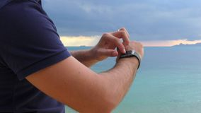 Close-up of a man `s hand with smart watch, uses a smart watch on the sea background. 4K stock video