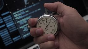 Close-up of man`s hand starting up a stopwatch at hacker programmer screen background. Deadline concept. 4K, 10 BIT, 4:2