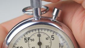 Close up of man`s hand starting up a stopwatch at white background