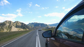 Close up of man`s hand on the steering wheel driving a car from side of car mirror mountain valley. Beautiful landscape Stock Images