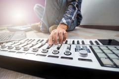 Close up man`s hand on synth panel in home music studio Stock Photos
