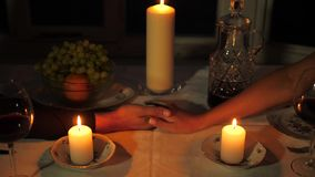 Close up Of Man`s Hand Takes The Woman`s Hand Over The Table Candles. Close-up of men`s hands take women`s hands, then begins to caress their fingers. They hold stock video footage