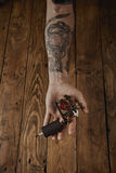 Close up of a man`s hand with tattoo gun. Close up of a man`s hand offers new custom made induction tattoo gun for coloring with rose graphic royalty free stock photography