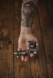 Close up of a man`s hand with tattoo gun. Close up of a man`s hand offers new custom made shiny metal tattoo gun on camera, above rustic wooden table stock images
