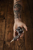 Close up of a man`s hand with tattoo gun. Close up of a man`s hand offers new custom made steampunk style tattoo gun above brushed vintage wooden table royalty free stock photography