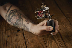 Close up of a man`s hand with tattoo gun. Close up of a man`s hand presented new custom made induction tattoo gun for coloring with rose graphic royalty free stock image