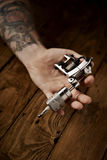 Close up of a man`s hand with tattoo gun. Close up of a man`s hand presented new custom made shiny metal tattoo gun royalty free stock photos