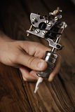 Close up of a man`s hand with tattoo gun. Close up of a man`s hand with a professional custom made induction tattoo gun royalty free stock image