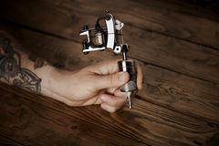 Close up of a man`s hand with tattoo gun. Close up of a tattooed man`s hand with a professional tattoo gun stock photo