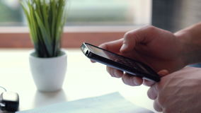 Close up of man's hand using smart phone. At the bar and blurred background stock video footage