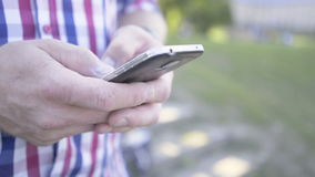 Close up on man`s hands browsing smartphone. Slider shot. stock video footage