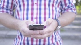 Close up on man`s hands browsing smartphone. Slider shot stock footage