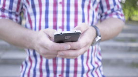 Close up on man`s hands browsing smartphone. Slider shot stock video footage