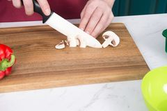 Close up of Man`s hands cut mushrooms with white knife on cutting board. Cha. Mpignon cut for salad by chef hands. Champignon lies on cutting board and cut by Stock Image