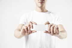 Close-up of man`s hands holding a business card, guy wearing white t-shirt. White background in studio.  Royalty Free Stock Images