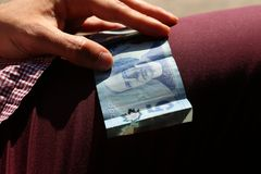 A close up of a man`s hands holding Canadian money- $100 bill royalty free stock photos